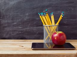 43327644 - back to school background with tablet, pencils and apple over chalkboard