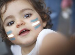 103999677 - kid fan with argentina flag painted on face