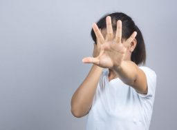 78193436 - woman hand doing a stop gesture on grey background