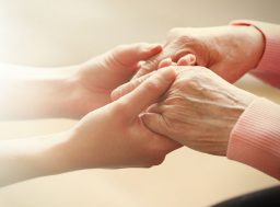 37056637 - old and young holding hands on light background, closeup